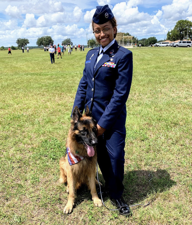 Cadet Chief Master Sergeant Thomas stands with a German Shepherd at a Civil Air Patrol activity.